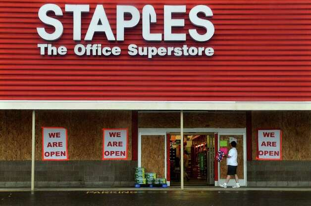 Even though windows are covered in plywood the Stapes store in The Dock shopping center remains open in Stratford, Conn. on Saturday August 27, 2011. Photo: Christian Abraham / Connecticut Post