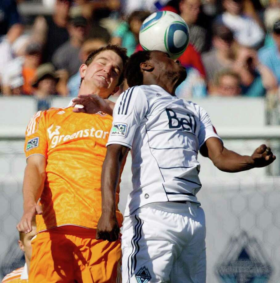The Dynamo's Bobby Boswell, left, and Vancouver's Mustapha Jarju jump for the ball during the first half. Photo: Darryl Dyck, Associated Press / The Canadian Press