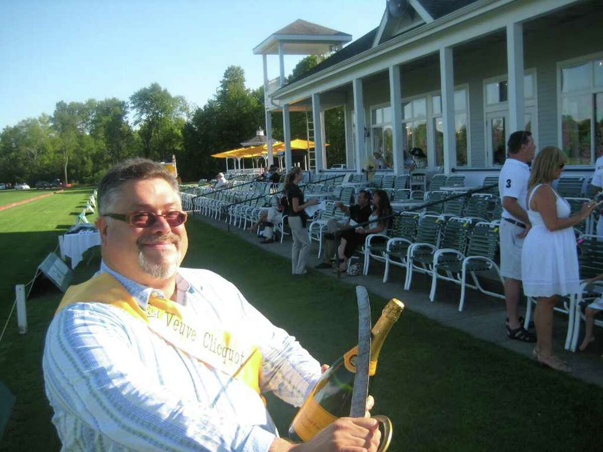 Jim Rossi at Saratoga Polo opening up a champagne bottle with a sword. (Leigh Hornbeck/Times Union)