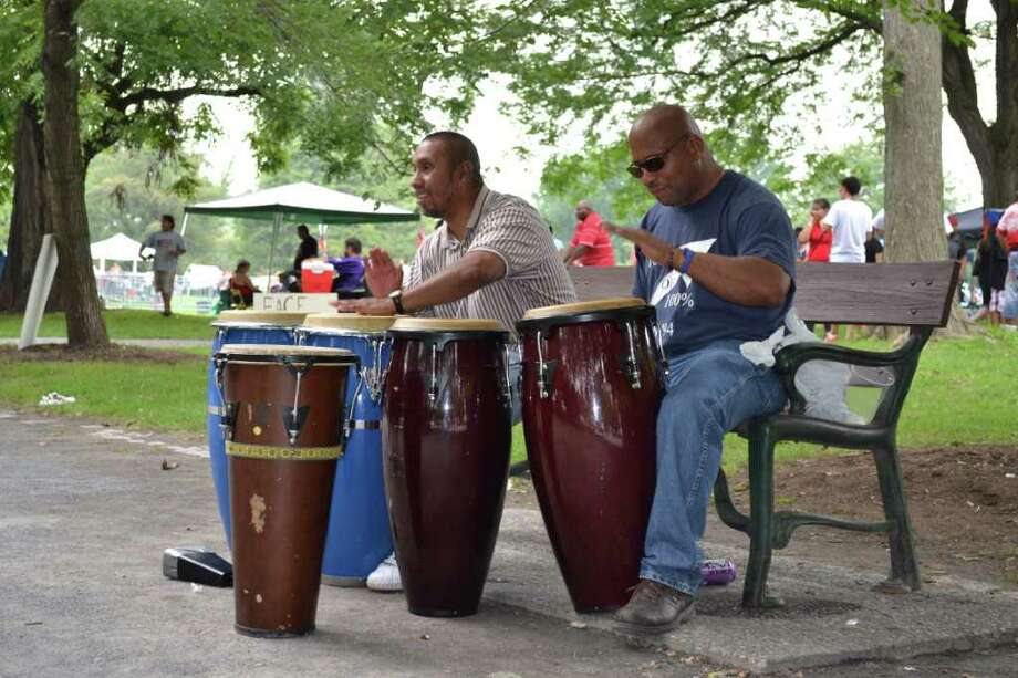 Manuel Mdeina, 45, Watervliet (left) and Jouse Tores, 48, of Albany, make their own music on the benches of Washington Park during Latin Fest.  (Kristi Gustafson Barlette/Times Union)