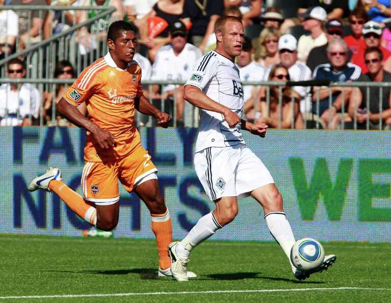 The Dynamo's Carlo Costly pursues Vancouver's Jay DeMerit during the match.