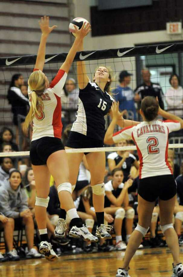College Park sophomore middle blocker Alyssa McNeely pushes the ball past Lake Travis senior outside hitter Piper Toler, left, and senior middle blocker Kaci Eaton. Photo: Jerry Baker, For The Chronicle