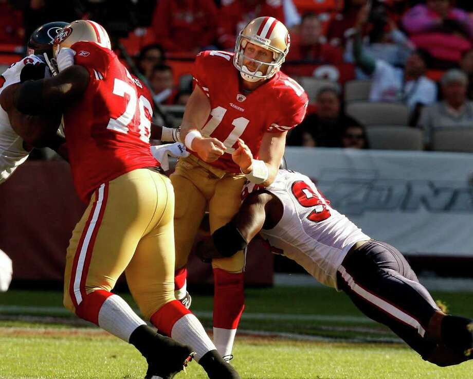 49ers quarterback Alex Smith absorbs a hit by two Texans linemen. Photo: Brant Ward, The Chronicle / SFC