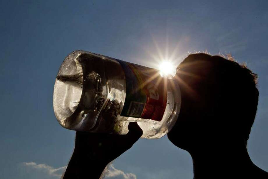 Chad Valentine tries to beat the heat with a drink of water at Alexander Deussen Park on Lake Houston on Saturday. Photo: Smiley N. Pool, Staff / © 2011  Houston Chronicle