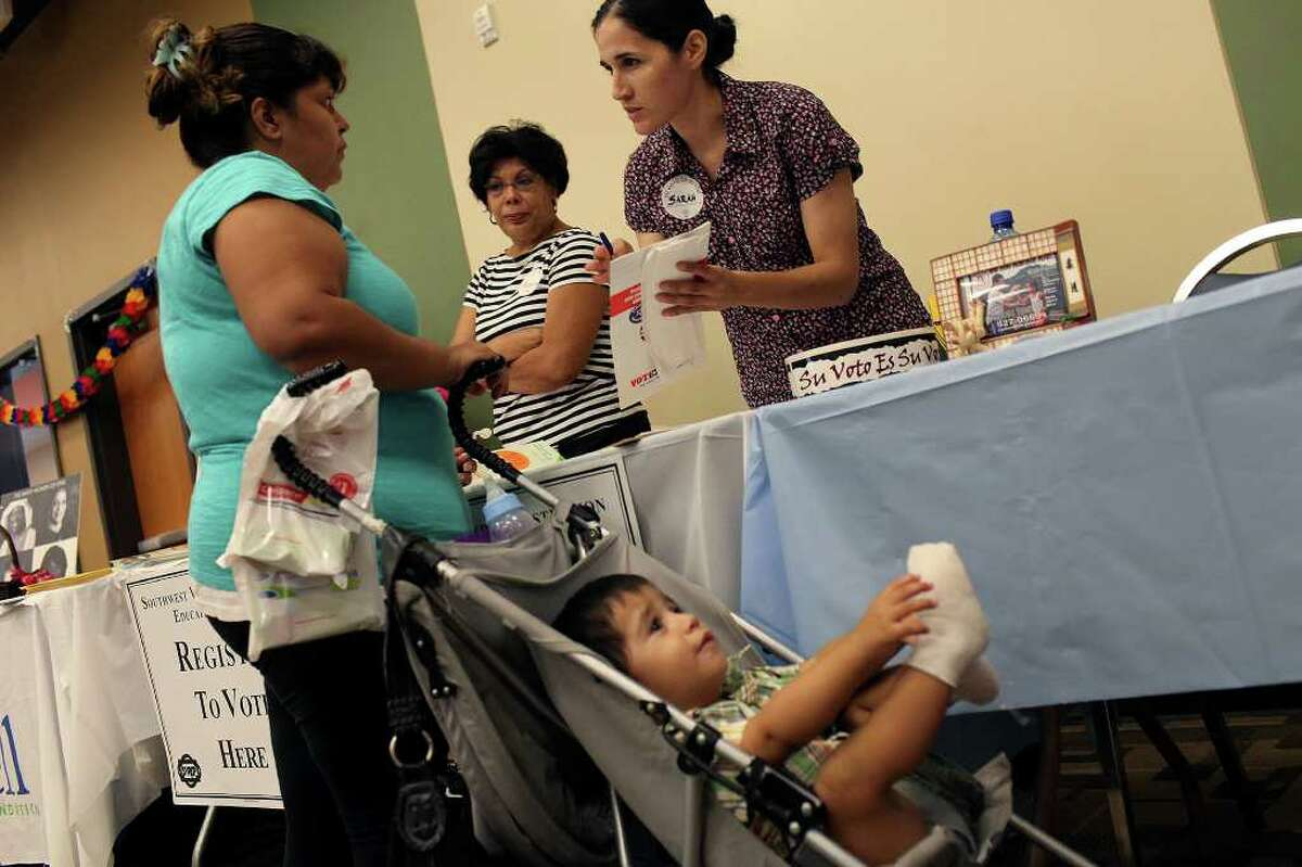Sarah Linares, right, Field Manager with the Southwest Voter Registration Education Project, registers Debra Hernandez, left, to vote while her son, Jeremiah Gomez, 1, waits during CentroMed's Back-to-School Health Assessment and Resource Fair at Southside Clinic on Saturday, August 6, 2011. Looking on is volunteer Maria Davalos-Salinas, center.