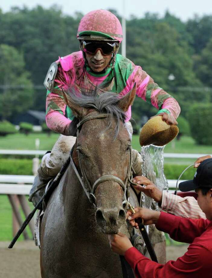 Jockey Rajiv Maragh grabs a sponge to cool off Caleb's Posseafter winning the 27th running of The Foxwoods Kiing's Bishop at the Saratoga Race Course in Saratoga springs, N.Y. Aug 27, 2011.  (Skip Dickstein / Times Union) Photo: SKIP DICKSTEIN