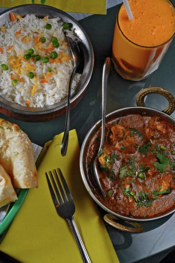 Methi Chicken, lower right, Basmat Rice, upper left, garlic naan, lower left, and a Mango Lassi drink, top, at Gandhi Indian Restaurant on Central Avenue on Monday Aug. 22, 2011 in Albany, NY. ( Philip Kamrass/ Times Union) Photo: Philip Kamrass / 00014347A