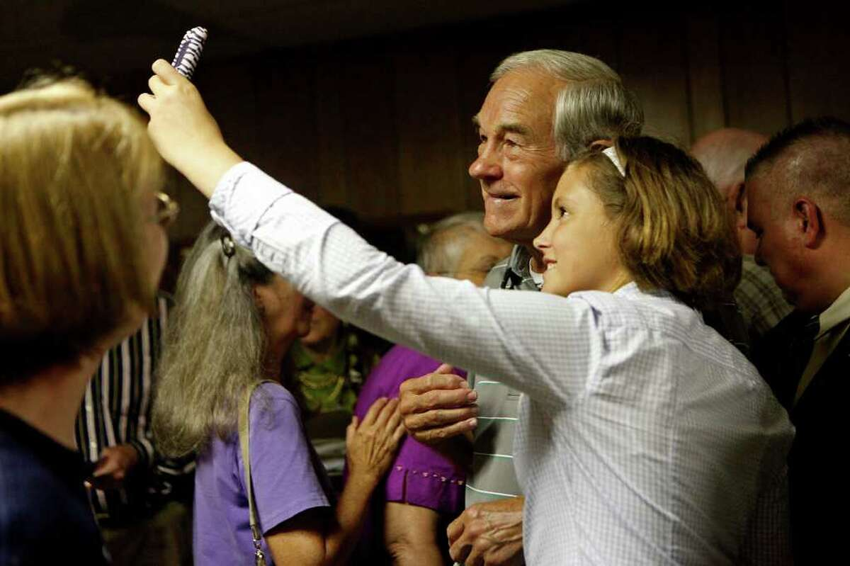 Gabby Harvey, 12, takes a photograph of herself with Congressman Ron Paul of Texas as he campaigns at the Northside Cafe in Winterset, IA on Saturday, August 27, 2011.