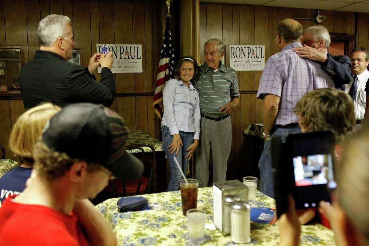 Congressman Ron Paul of Texas poses with Gabby Harvey, 12, as he campaigns at the Northside Cafe in Winterset, IA on Saturday, August 27, 2011.