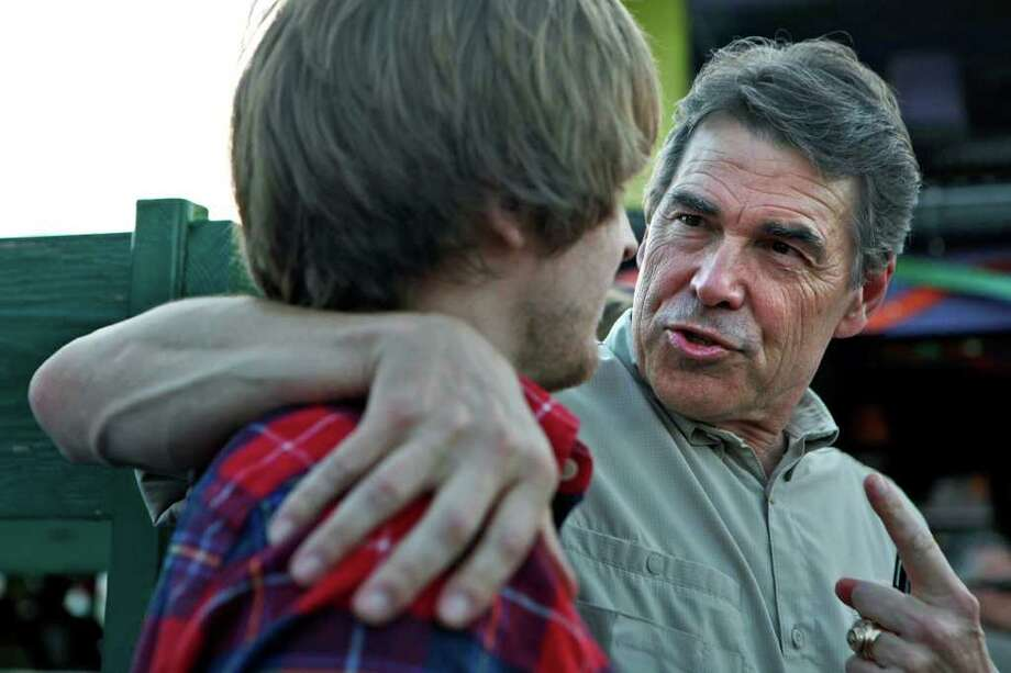 Governor Rick Perry talks to supporter Branden Lewiston, 19, of Indianola, IA, and a returning sophomore at Princeton University, as Perry campaigns at the Polk County Republicans Summer Picnic at Jalapeno Pete's at the Iowa State Fairgrounds in Des Moines, IA, on Saturday, August 27, 2011. Photo: LISA KRANTZ, LISA KRANTZ/lkrantz@express-news.net / SAN ANTONIO EXPRESS-NEWS