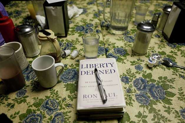 Congressman Ron Paul's book waits to be signed for supporter Lexy Nuzum as Paul campaigns at the Northside Cafe in Winterset, IA on Saturday, August 27, 2011. Photo: LISA KRANTZ, LISA KRANTZ/lkrantz@express-news.net / SAN ANTONIO EXPRESS-NEWS