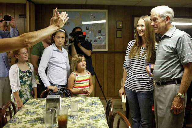 Lexy Nuzum poses for a photo with Congressman Ron Paul as  he campaigns at the Northside Cafe while Emma Gallagher, 8, Gabby Harvey, 12, and Mary Lininger, 6, watch in Winterset, IA on Saturday, August 27, 2011. Photo: LISA KRANTZ, LISA KRANTZ/lkrantz@express-news.net / SAN ANTONIO EXPRESS-NEWS