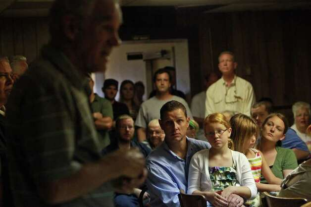 Michael Gallagher, of Winterset, IA, with his wife, Michaelle Gallagher, right, and their daughters, Emma Gallagher, 8, and Mary Lininger, 6, listen as Congressman Ron Paul, left, speaks at the Northside Cafe in Winterset, IA on Saturday, August 27, 2011. Photo: LISA KRANTZ, LISA KRANTZ/lkrantz@express-news.net / SAN ANTONIO EXPRESS-NEWS