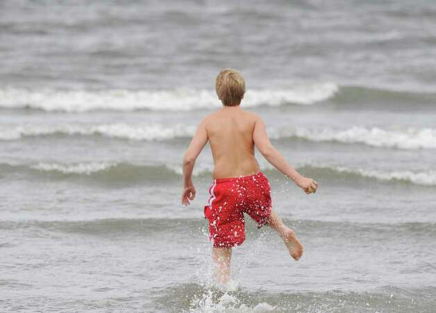 Matthijs Hoekstra, 14, of Greenwich, runs into Long Island Sound at Greenwich Point, Saturday afternoon, Aug. 27, 2011.  Hurricane Irene is expected to hit the area Sunday. Photo: Bob Luckey / Greenwich Time