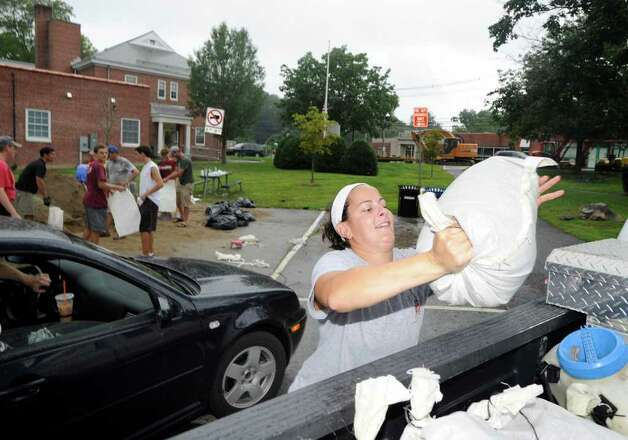 Amy Bologna, 31, of Pemberwick, loads sandbags into a vehicle in preparation for Hurricane Irene at the Glenville Fire Station, Saturday afternoon, Aug. 27, 2011. Photo: Bob Luckey / Greenwich Time