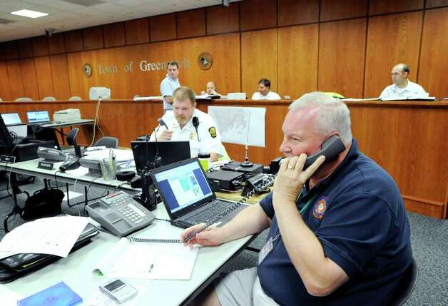 Greenwich Emergency Management Director Dan Warzoha, right, gets an updated hurricane forecast over the phone at the emergency operations center at Greenwich Town Hall, Saturday afternoon, Aug. 27, 2011. Photo: Bob Luckey / Greenwich Time