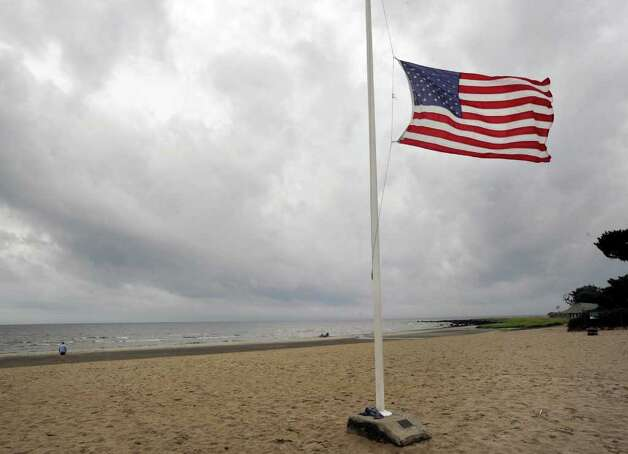 Under a dark, cloudy sky, the American flag blows in the wind at a deserted Greenwich Point, Saturday afternoon, Aug. 27, 2011.  Hurricane Irene is expected to hit the Greenwich area Sunday. Photo: Bob Luckey / Greenwich Time