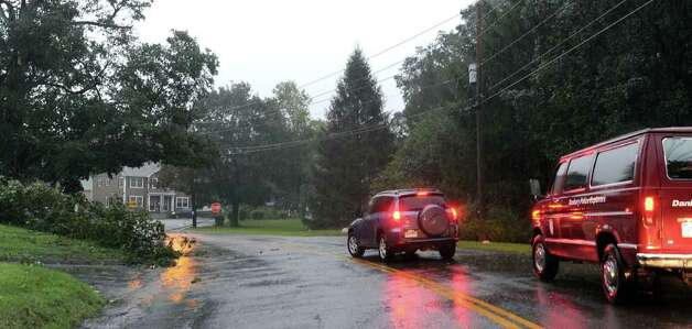 Cars hesitate to cross under downed wires on Coalpit Hill Road in Bethel Sunday morning. The wires were brought down by tree branches that had fallen in the heavy rain and wind of Hurricane Irene. Photo: Carol Kaliff