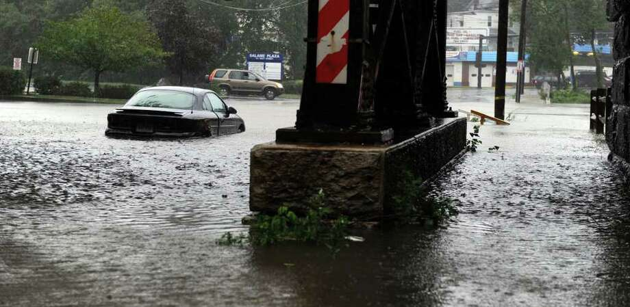 A car is stuck in the fllood water under the West Street bridge in Danbury Sunday morning. Hurricane Irene is bringing heavy rains and wind to the area. Photo taken Sunday, Aug. 28, 2011. Photo: Carol Kaliff