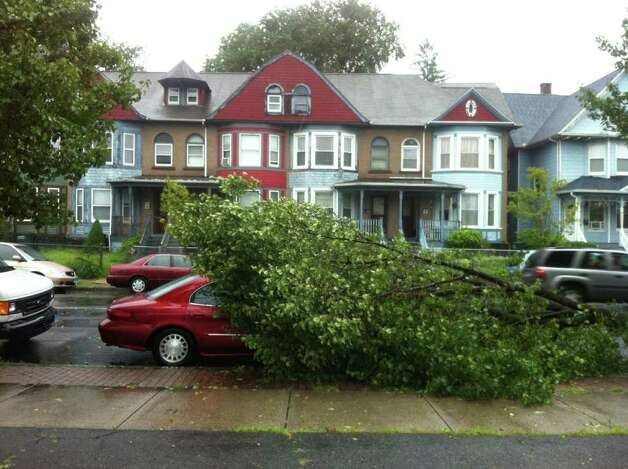A tree fell on a car on State Steet in Bridgeport, Conn. as a result of winds brought by Hurricane Irene on Sunday, August 28, 2011. Photo: Brett Mickelson