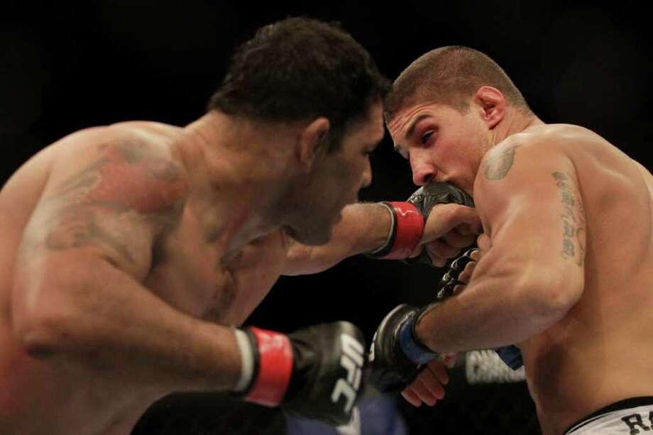 Minotauro Nogueira reaches out for a punch against Brendan Schaub. Photo: Felipe Dana, Associated Press / AP