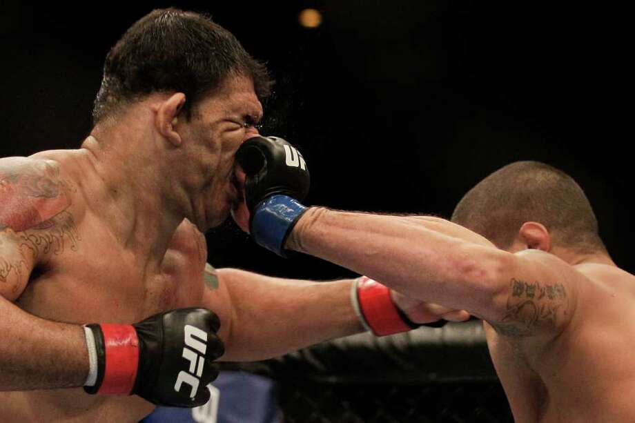 Minotauro Nogueira takes a punch in an exchange with Brendan Schaub. Photo: Felipe Dana, Associated Press / AP
