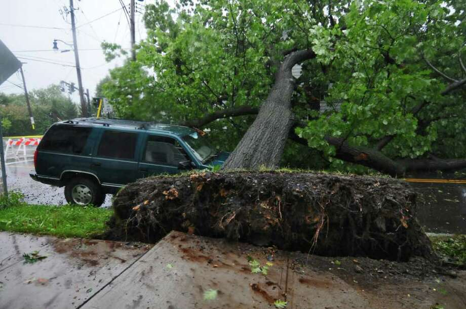 "A tree fell across a truck owned by James Terrell on Mereline Avenue as a result of Hurricane Irene at 6:30 a.m. on Sunday Aug. 28, 2011,  in Albany, NY.  ""I was making a cup of coffee, and I heard a big crack,"" said Terrell. The tree fell to his house, and partially covered another vehicle parked there. He and his family were without power as of noon. (Philip Kamrass / Times Union) Photo: Philip Kamrass"