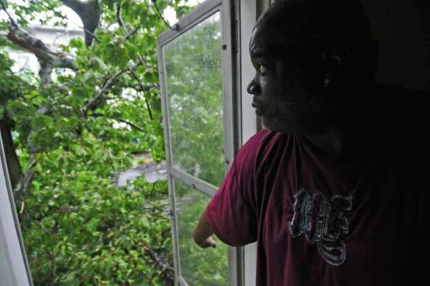 "James Terrell looks out of his house at the remains of a tree that fell on his truck parked on Mereline Avenue as a result of Hurricane Irene at 6:30 am on Sunday Aug. 28, 2011,  in Albany, NY.  ""I was making a cup of coffee, and I heard a big crack,"" said Terrell. The tree fell to his house, and partially covered another vehicle parked there. He and his family were without power as of noon. (Philip Kamrass / Times Union) Photo: Philip Kamrass"