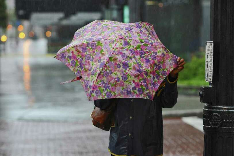 A pedestrian tries to stay dry on North Pearl Street during Hurricane Ireneon Sunday Aug. 28, 2011,