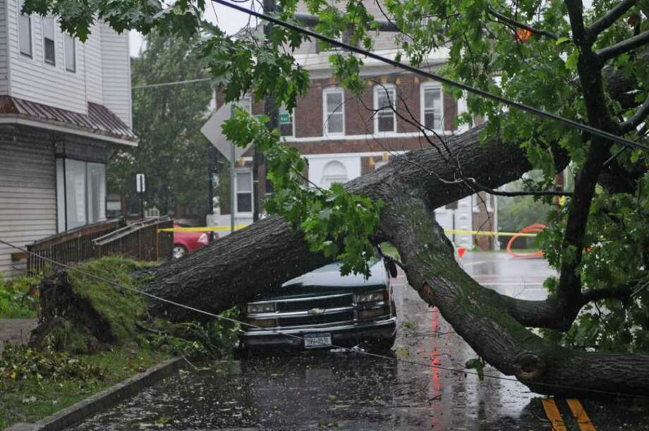 """A tree fell across a truck owned by James Terrell on Mereline Avenue as a result of Hurricane Irene at 6:30 am on Sunday Aug. 28, 2011,  in Albany, NY.  """"I was making a cup of coffee, and I heard a big crack,"""" said Terrell. The tree fell to his house, and partially covered another vehicle parked there. He and his family were without power as of noon. (Philip Kamrass / Times Union) Photo: Philip Kamrass"""