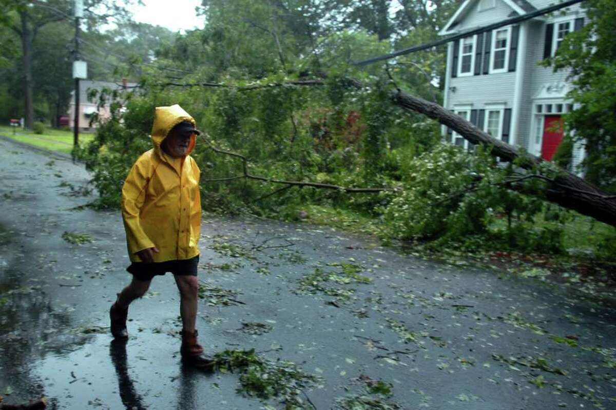 Rick Capozzi walks near downed trees and power line on Pumpkinground Rd. in Stratford, Conn. Aug. 28th, 2011.