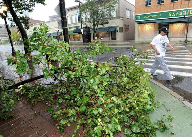 Manuel Mercado of Stamford works past a downed tree limb on Atlantic Street in downtown Stamdford during Hurricane Irene, Sunday morning, Aug. 28, 2011. Photo: Bob Luckey / Greenwich Time