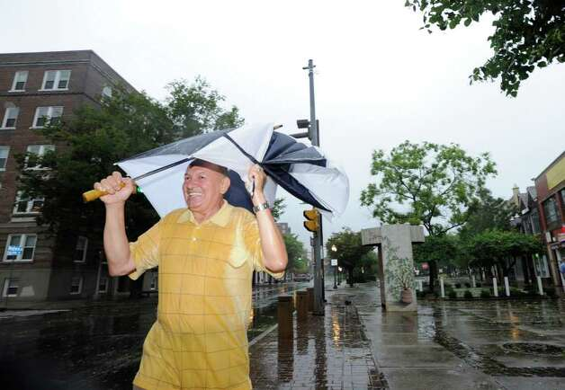 Efrin Gutirrez of Stamford wears a smile on his face as he clutches his umbrella while walking down Bedford Street during the high winds of Hurricane Irene in downtown Stamford, Sunday morning, Aug. 28, 2011. Photo: Bob Luckey / Greenwich Time