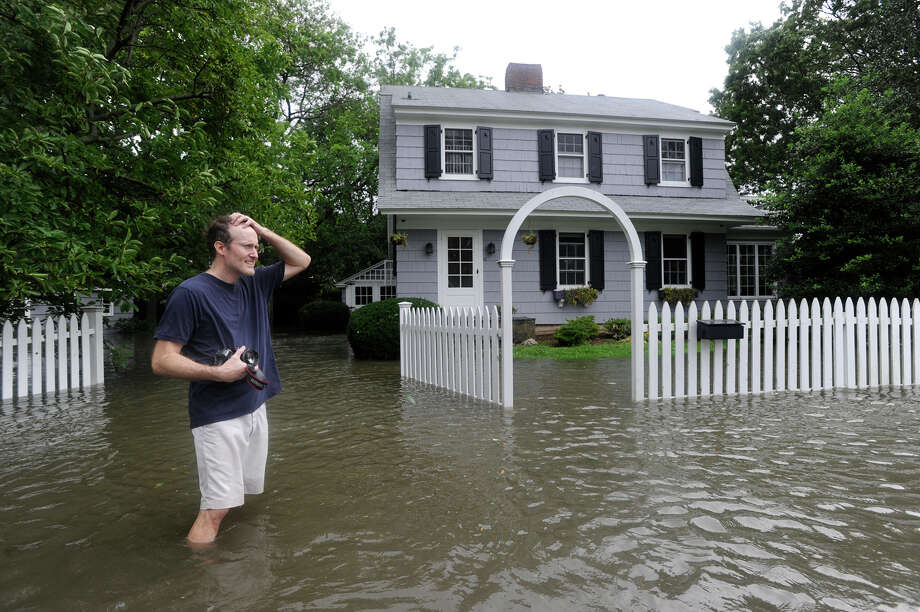 A man who would give his name as only Charlie puts his hand to his head in front of his flooded Meadowbank Road home in Old Greenwich during Hurricane Irene Sunday morning, Aug. 28, 2011. / Greenwich Time