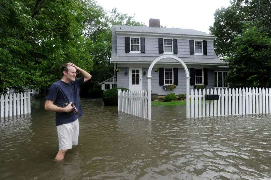 A man who would give his name as only Charlie puts his hand to his head in front of his flooded Meadowbank Road home in Old Greenwich during Hurricane Irene Sunday morning, Aug. 28, 2011. Photo: Bob Luckey, Greenwich Time / Greenwich Time