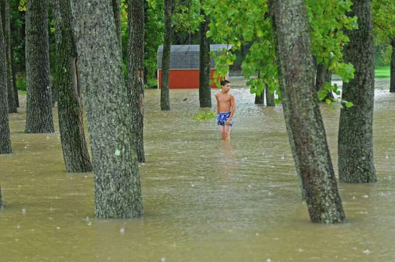 Cory Smith, 14, of Coeymans Landing checks the depth of water near a parking lot at the landing's fi