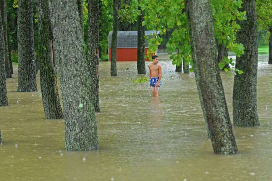 Cory Smith, 14, of Coeymans Landing checks the depth of water near a parking lot at the landing's fishing access point to the Hudson River as a result of Hurricane Irene on Sunday, Aug. 28, 2011,  in Albany, NY.  He estimated the water to be about one and a half feet deep. He had stepped out of his nearby home for the first time during the storm.  (Philip Kamrass / Times Union) Photo: Philip Kamrass