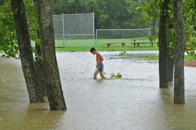 Cory Smith, 14, of Coeymans Landing checks the depth of water near a parking lot at the landing's fishing access point to the Hudson River,  as a result of Hurricane Irene on Sunday Aug. 28, 2011,  in Albany, NY.  He estimated the water to be about 1 1/2 feet deep. He had stepped out of his nearby home for the first time during the storm.  (Philip Kamrass / Times Union) Photo: Philip Kamrass