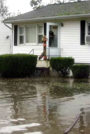 A West Haven firefighter knocks on a door looking for stranded residents along Thomas Street in West Haven, Conn. on Sunday August 28, 2011. The West Haven firefighters used a boat to go door to door. Photo: Christian Abraham