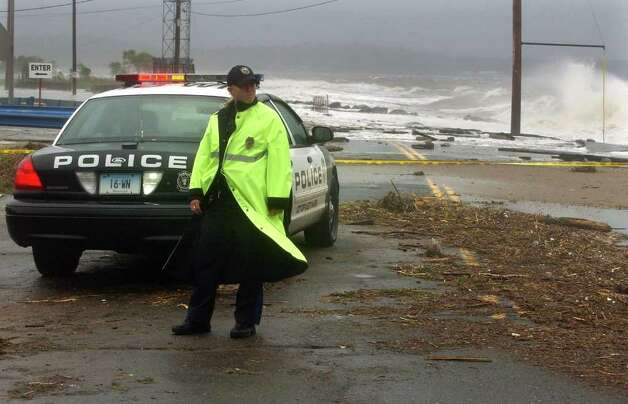 A West Haven police officer stands watch along a closed Beach Avenue in West Haven, Conn. on Sunday August 28, 2011. Photo: Christian Abraham