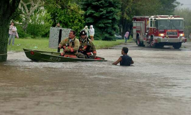 West Haven firefighters use a boat to go door to door looking for stranded residents along Morse Street in West Haven, Conn. on Sunday August 28, 2011. Photo: Christian Abraham
