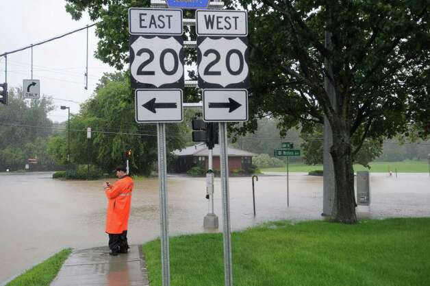 A Guilderland police officer looks over the flooded intersection of Fuller Road and Western Avenue as a result of Hurricane Irene on Sunday Aug. 28, 2011,  in Guilderland, NY.    (Philip Kamrass / Times Union) Photo: Philip Kamrass