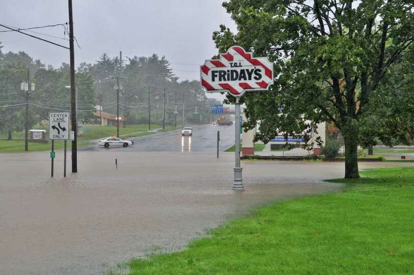 A Guilderland police car stops traffic at the flooded intersection of Fuller Road and Western Ave
