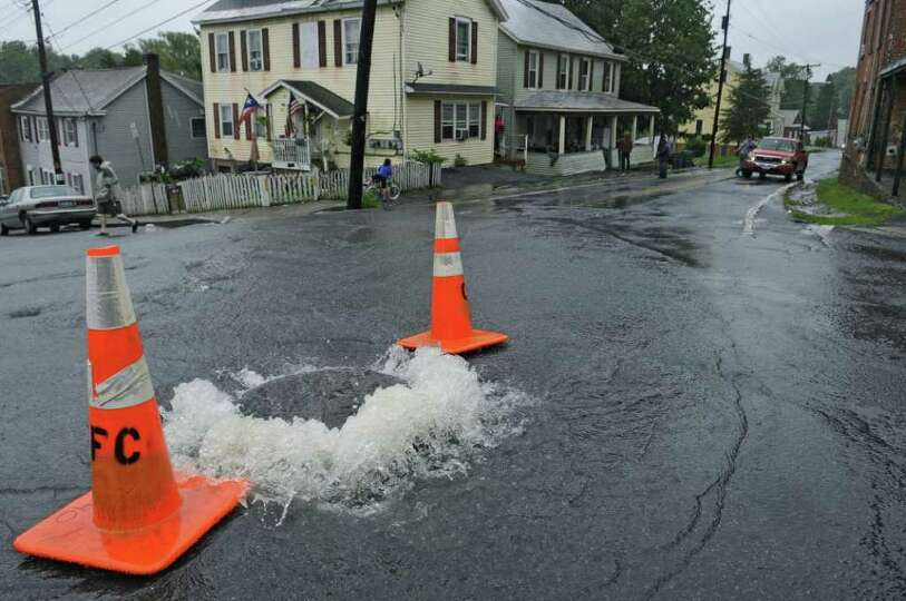 A manhole cover is overwhelmed by water at the intersection of Main  and Westerlo streets as a resul