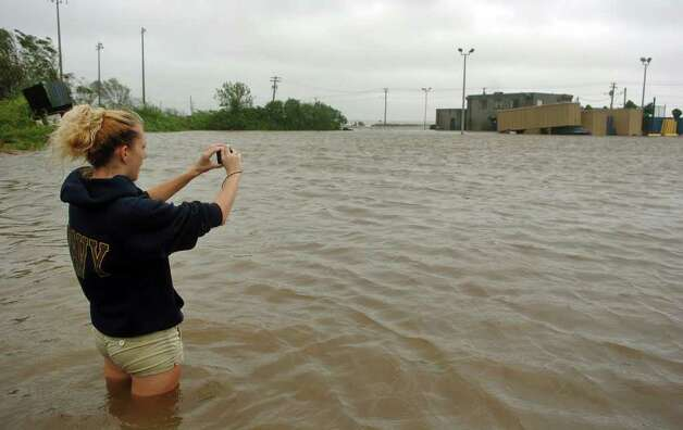 A local resident takes pictures of a flooded Chick's restaurant along Beach Avenue in West Haven, Conn. on Sunday August 28, 2011. Photo: Christian Abraham