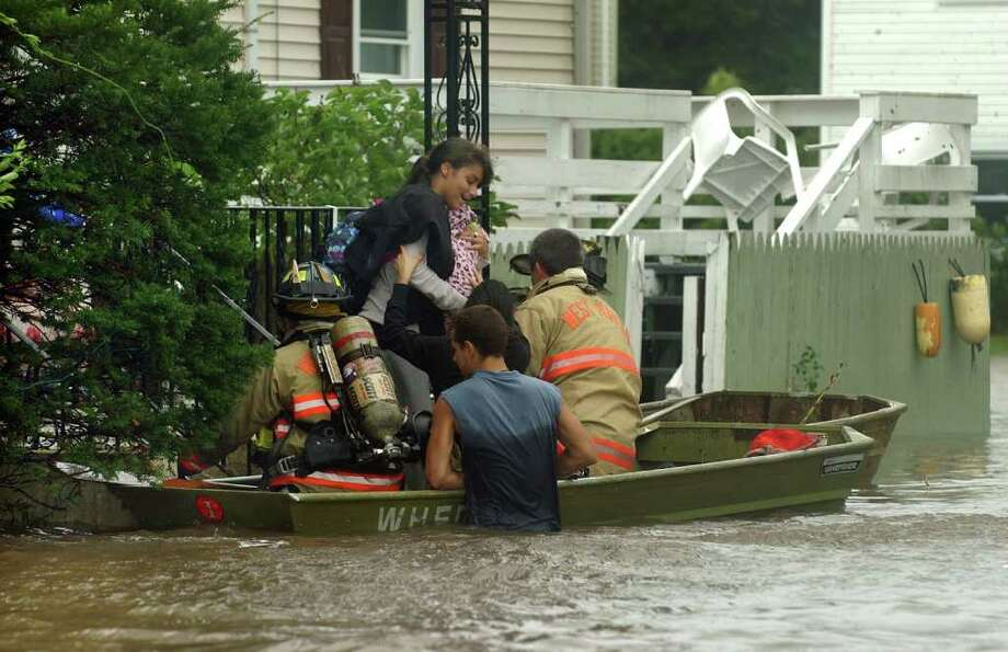 A local resident is rescued from her home by West Haven firefighters along Morse Street in West Haven, Conn. on Sunday August 28, 2011. Photo: Christian Abraham