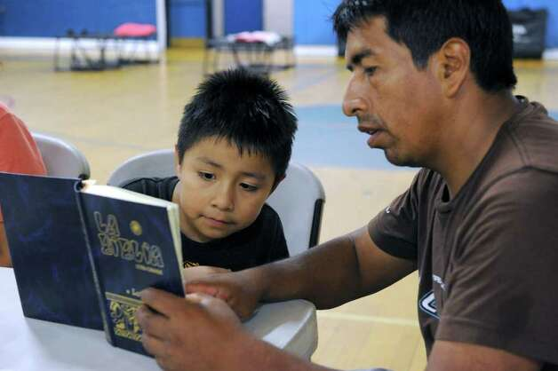 Claudio Pulla of Danbury, reads the Bible to his son Elmer, 6, to help pass the time at the emergency shelter at Rogers Park Sunday. Pulla took his family to the shelter Sunday night because he has large trees in his back yard and he was afraid they would topple over in the winds and rain of Tropical Storm Irene. Photo taken Sunday, August 28, 2011. Photo: Carol Kaliff