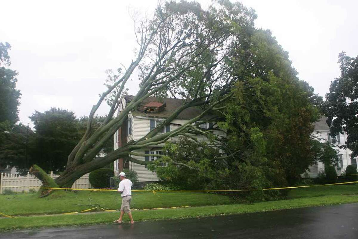 A tree hits a home on the corner of Midland St. and Lake Ave. during hurricane Irene in Black Rock in Bridgeport on Sunday August 28, 2011.