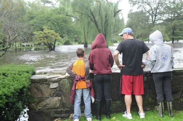 Antonio, 11, Gabriella, 16, Richard and Mafalada DiLorenzo look at  the flooded Binney Park at Old Greenwich during Hurricane Irene on Sunday, Aug. 28. 2011. Photo: Helen Neafsey / Greenwich Time