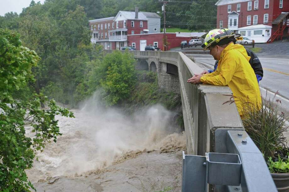 Coeymans Fire Chief Ken Dottino watches the raging Coeymans Creek from Route 144 as a result of Tropical Storm Irene on Sunday Aug. 28, 2011,  in Coeymans, NY.  He said they had responded to 30 calls between  8 a.m., and 4:30 p.m. (Philip Kamrass / Times Union) Photo: Philip Kamrass